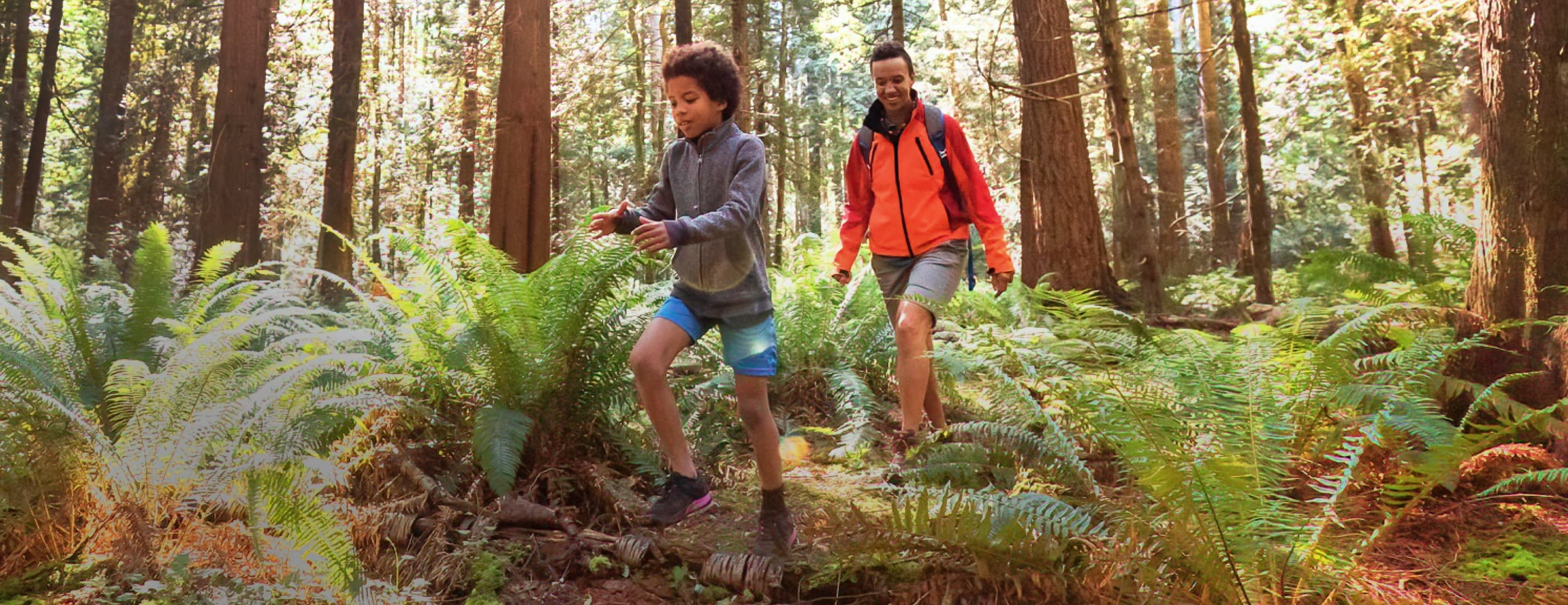 An adult in an orange raincoat and a child in a grey sweatshirt with dark hair are hiking through a forest, the adult smiles as the child skips over a small log on the trail.
