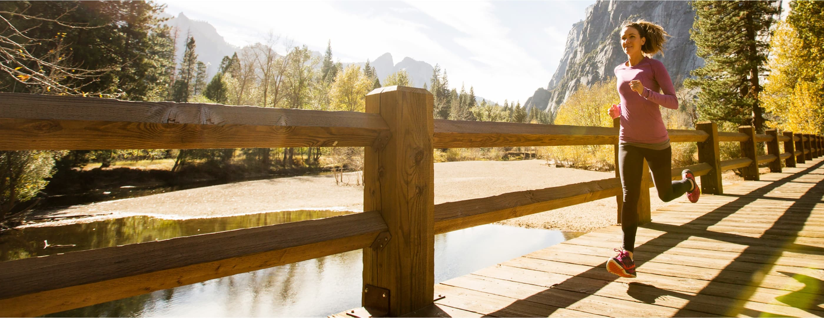 A runner with curly brown hair in a ponytail wearing a pink sweatshirt crosses a boardwalk bridge in front of towering rocky peaks.