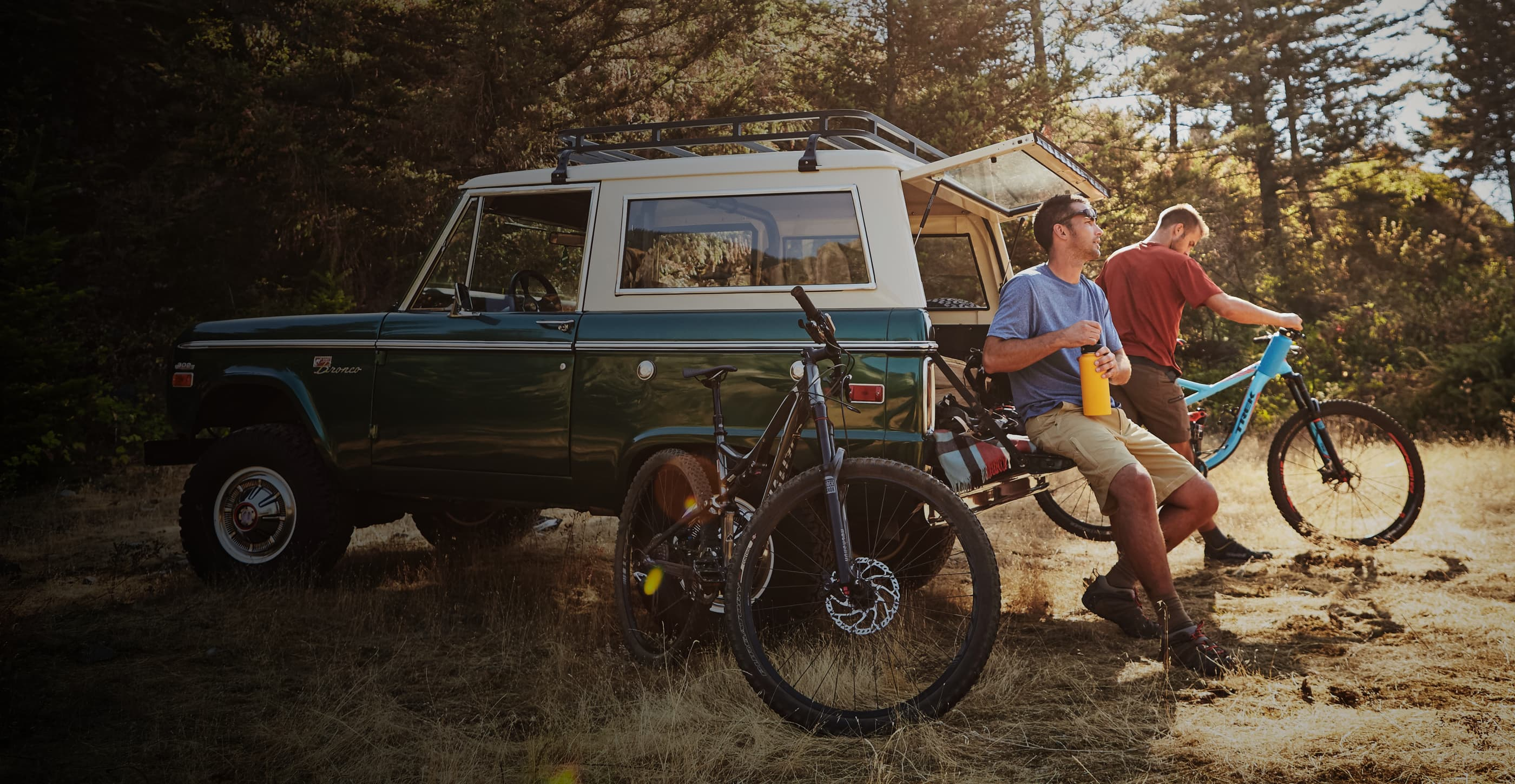 A biker with short brown hair and sunglasses sits on the tailgate of a green and white Ford Bronco opening a yellow water bottle, and another biker with short blond hair stands next to them inspecting a bright blue mountain bike. The vehicle is parked in a grassy field surrounded by trees and a black mountain bike leans against its side.
